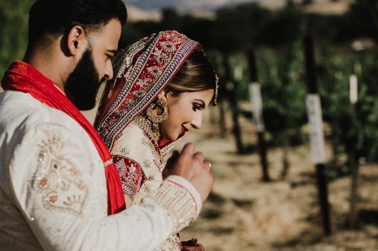 indian bride and groom walking through vineyard