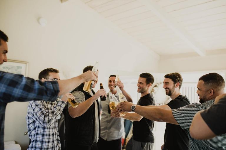 groom and groomsmen toasting before wedding