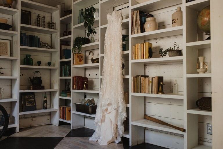 casablance 2392 bridal gown hanging on bookshelf