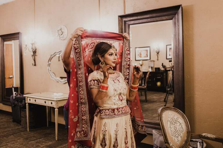 indian bride has her dupatta placed on her head